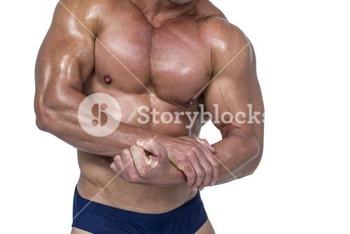 Midsection of shirtless man flexing  muscles