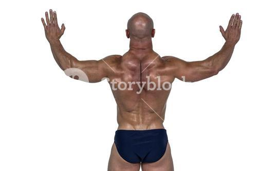 Rear view of muscular man with arms raised