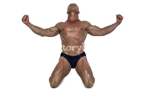 Muscular man kneeling down with arms outstretched
