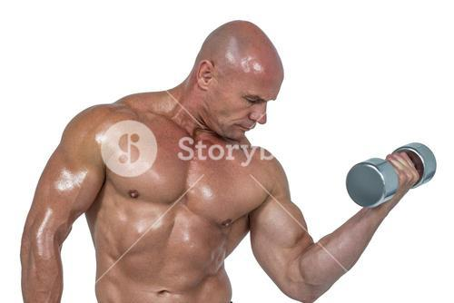 Bodybuilder concentrating while lifting dumbbells