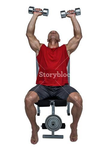 Healthy man lifting dumbbells while sitting on bench press