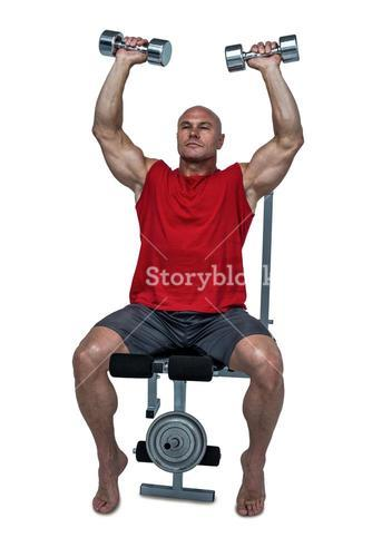 Muscular man exercising while sitting on bench press