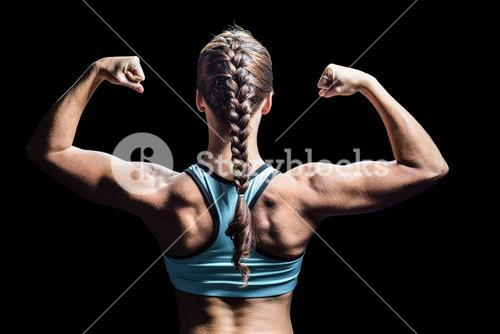 Rear view of woman with braided hair flexing muscles