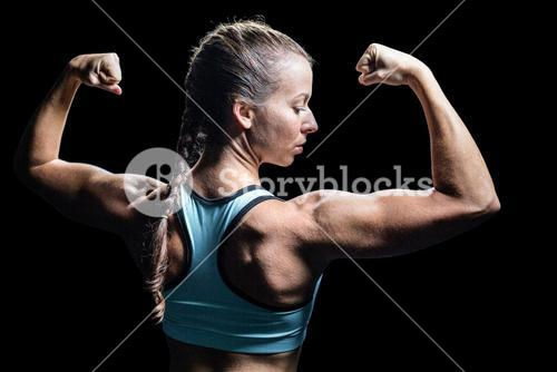Athlete woman flexing muscles