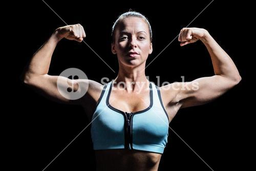 Thoughtful athlete flexing muscles