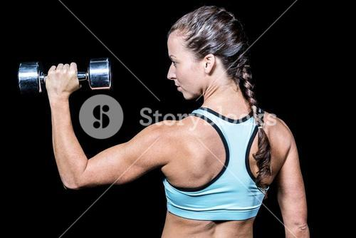 Rear view of woman lifting dumbbell