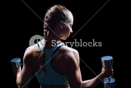 Rear view of woman exercising with dumbbells
