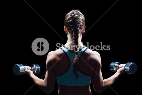 Rear view of braided hair woman lifting dumbbells