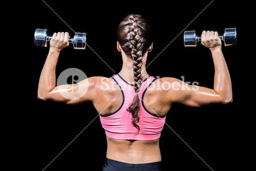 Rear view of braided hair woman exercising dumbbells