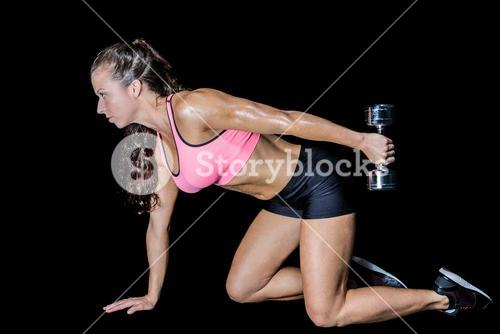 Side view of woman kneeling while lifting dumbbell