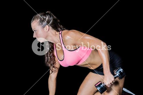 Side view of kneeling while exercising with dumbbell