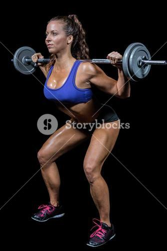 Woman crouching while lifting