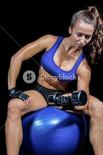 Thoughtful woman lifting dumbbell while sitting on exercise ball