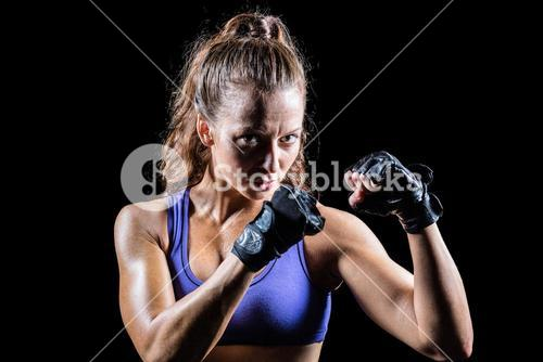 Portrait of female confident boxer with fighting stance