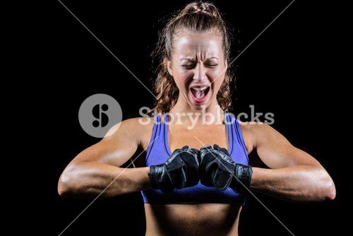 Aggressive female boxer flexing muscles