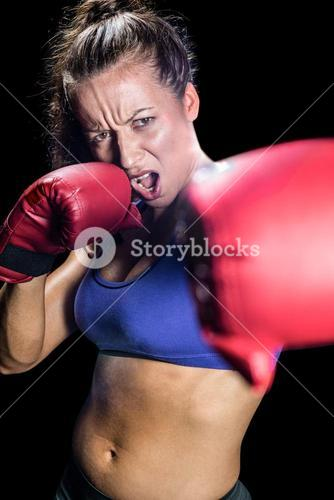 Portrait of aggressive female boxer with fighting stance