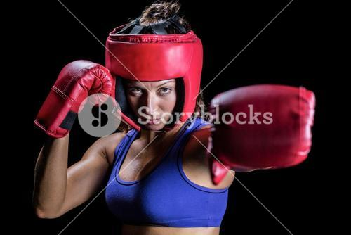 Portrait of female boxer with gloves and headgear