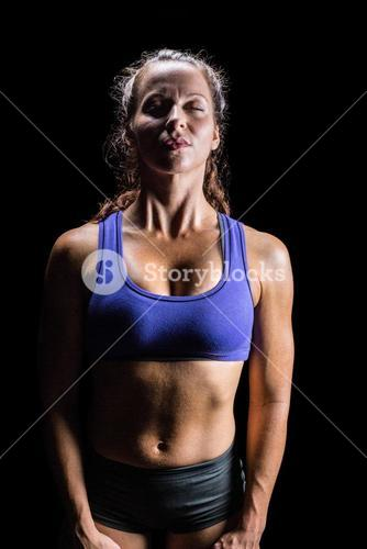 Athlete relaxing against black background