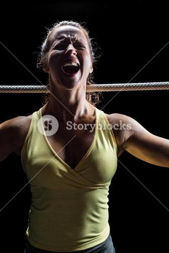 Angry woman screaming while holding rope