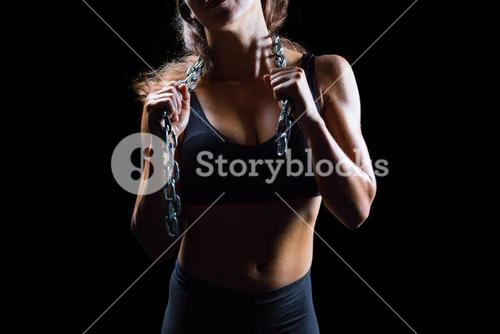 Midsection of female athlete with chain