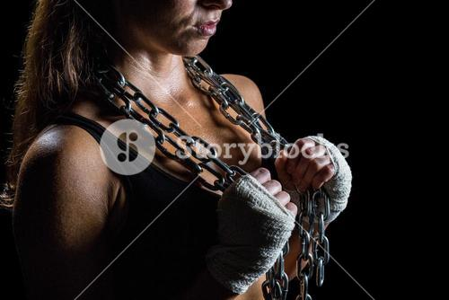 Midsection of female athlete holding chain