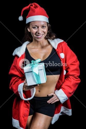 Portrait of female athlete holding Christmas gift with hand on hip