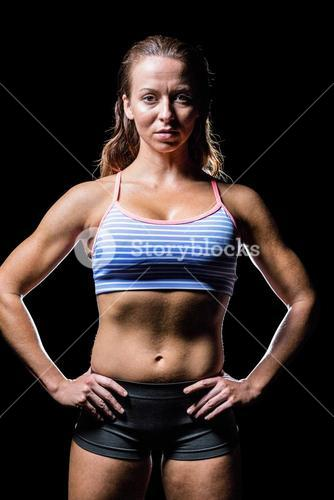 Portrait of female athlete with hands on hip