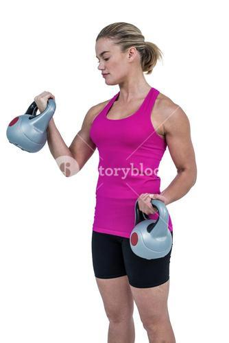 Muscular woman exercising with kettlebells