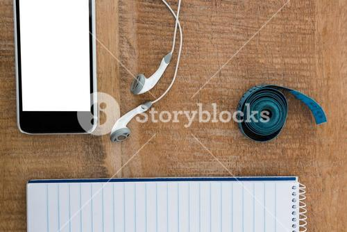 Notepad with smartphone and measuring tape