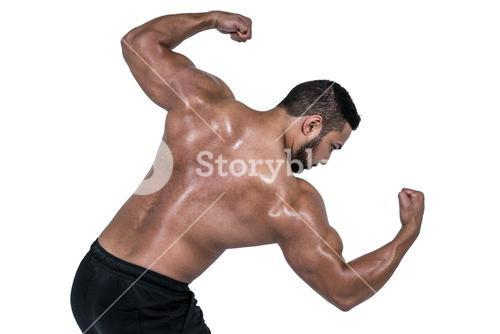 Muscular man flexing for camera