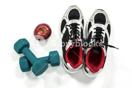 Shoes dumbbells and an apple
