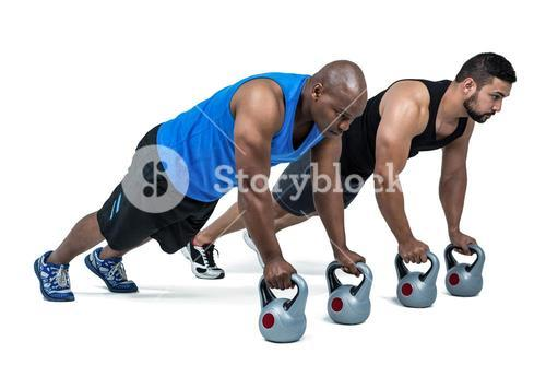 Strong friends using kettlebells together