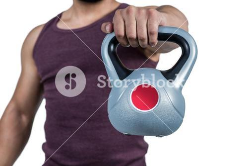 Mid section of a muscular man holding a kettlebell