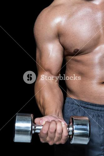 Mid section of a bodybuilder with dumbbell
