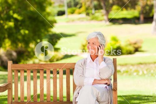 Elderly woman on a phone in a park