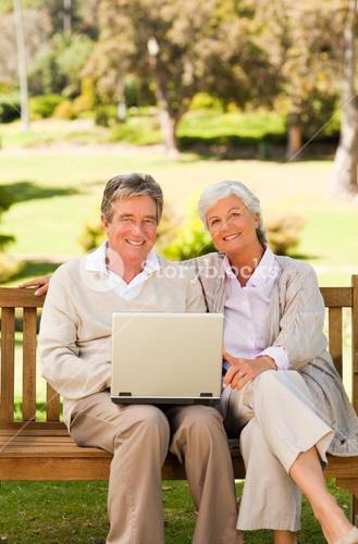 Couple working on their laptop in a park