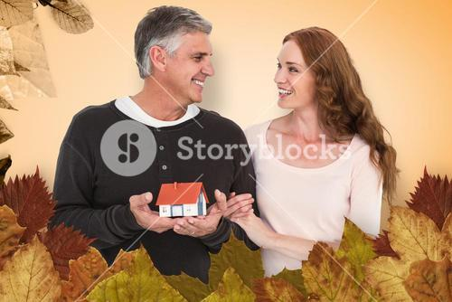 Composite image of casual couple holding small house