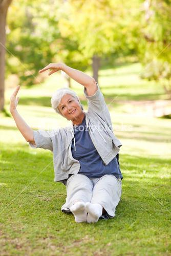 Senior woman doing her stretches in the park