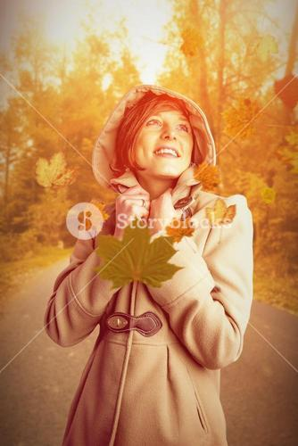 Composite image of smiling beautiful woman in winter coat looking up