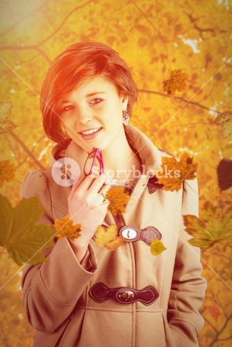 Composite image of portrait of pretty woman in winter coat holding glasses