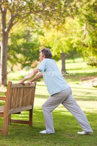 Retired man doing his stretches in the park