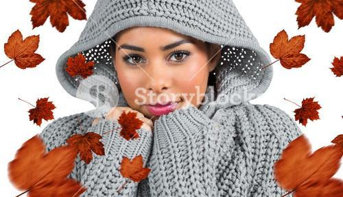 Composite image of pretty girl in winter jumper looking at camera