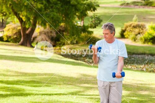 Elderly man doing his exercises in the park