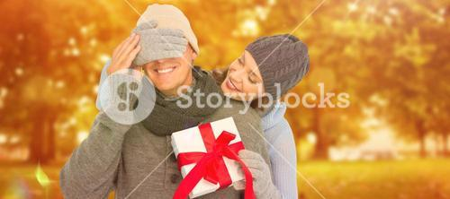 Composite image of woman surprising husband with gift