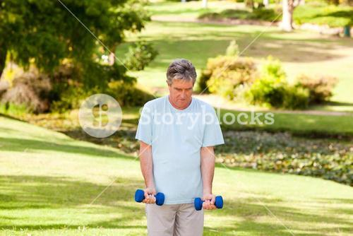 Mature man doing his exercises in the park