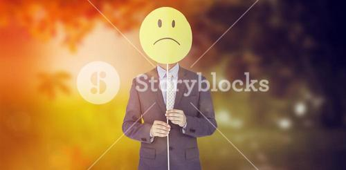 Composite image of businessman holding sad smiley in front of face