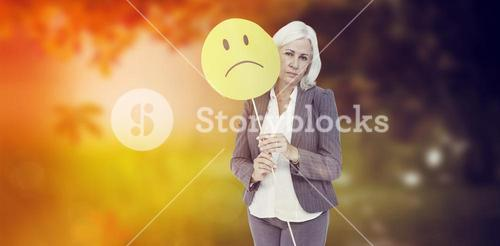 Composite image of  businesswoman holding sad smiley face