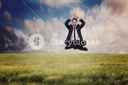 Composite image of businessman sitting in lotus pose with hands together