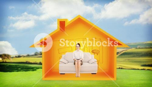 Composite image of smiling well dressed woman sitting on sofa