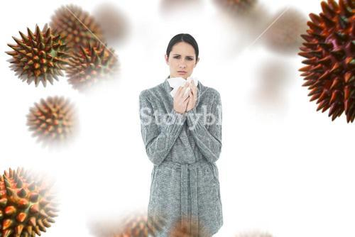 Composite image of portrait of a casual young woman suffering from cold